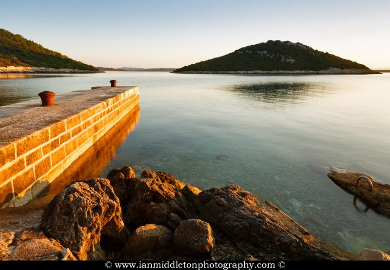 The morning sunrise casts warm light and colour over the rocky coastal area and pier of Cunski and casts a shadow over the island of Veli Osir. Cunski lies just 8kms north of Mali Losinj on Losinj Island, Croatia.