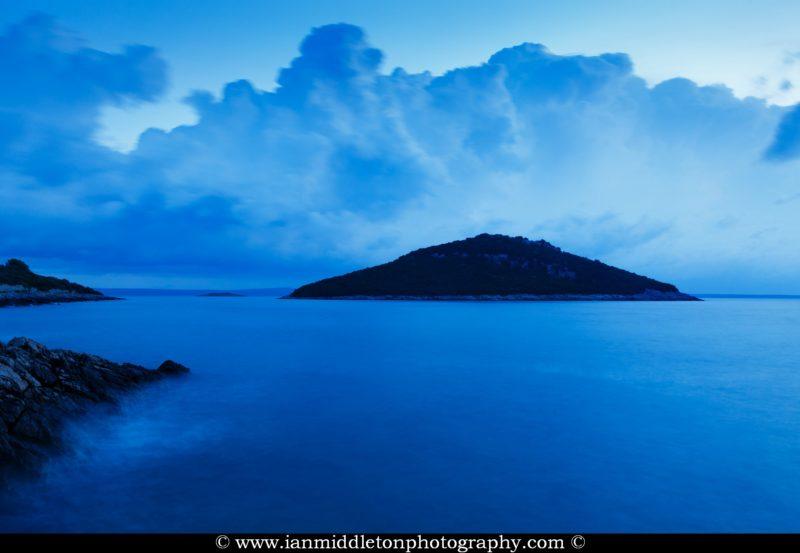 Storm moving in over Mali Osir and Veli Osir Island at dawn, seen from Zaosiri Beach, Cunski on Losinj Island, Croatia.