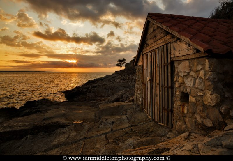 Sunrise over a boathouse on Osiri Beach on the coastal area of Cunski, which lies just 8kms north of Mali Losinj on Losinj Island, Croatia. The strip of land to the left is Punta Kriza.