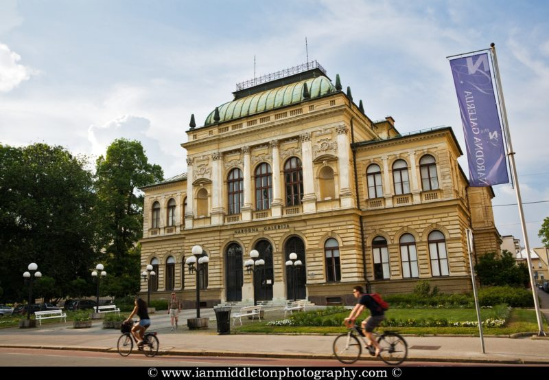 Late afternoon summer light falls on Ljubljana's National Gallery as two cyclists ride by. Narodna galerija (National Gallery of Slovenia) is the main art museum in Slovenia. It holds the largest visual arts collection from the late medieval period to the early twentieth century.