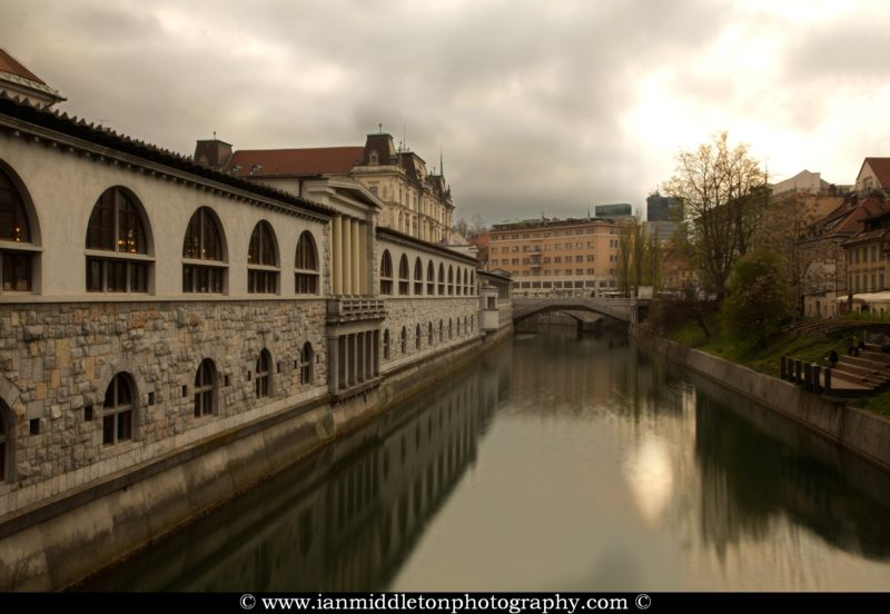 View across the Ljubljanica River that runs through the centre of Ljubljana, the capital of Slovenia. On the left you can see the Trznica (market place) and ahead is the famous Tromostovje (triple bridge), all designed by Slovenia's foremost architect, Joze Plecnik.