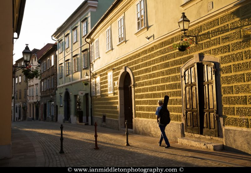 Musician carrying his guitar in Gornji Trg in the old town of Ljubljana, Slovenia at sundown.