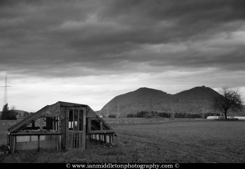Black and White photo of a dilapidated shed on an allotment on the northern outskirts of Ljubljana, Slovenia. You can see Smarna Gora mountain in the background, a popular hiking spot.