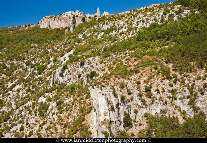 The parish church of the visitation of the holy virgin Mary and its 18th century bell tower in Lubenice village, Cres island, Croatia. Seen on the cliff from the trail that leads down to the beach.