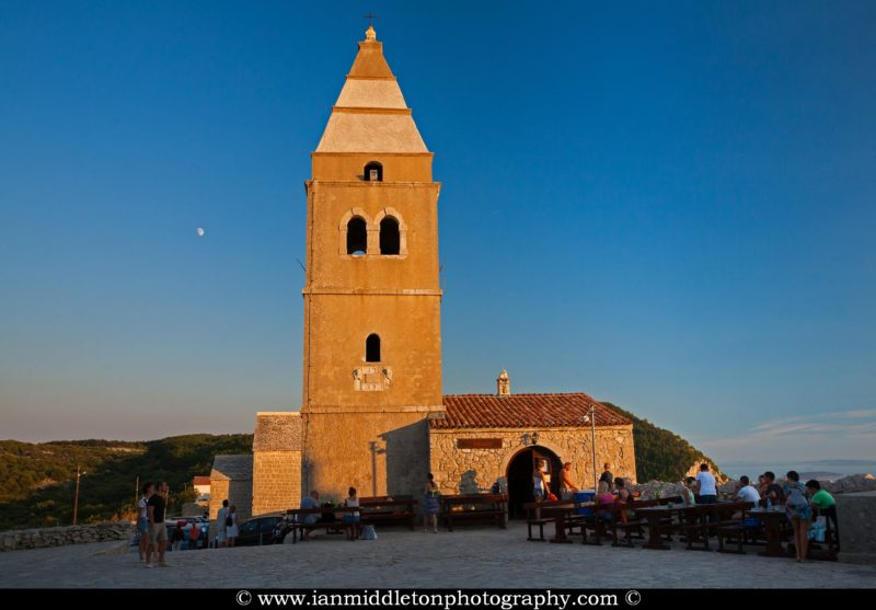 The parish church of the visitation of the holy virgin Mary and its 18th century bell tower in Lubenice village, Cres island, neighbouring Losinj Island, Croatia. The moon is rising behind the church just at sundown.