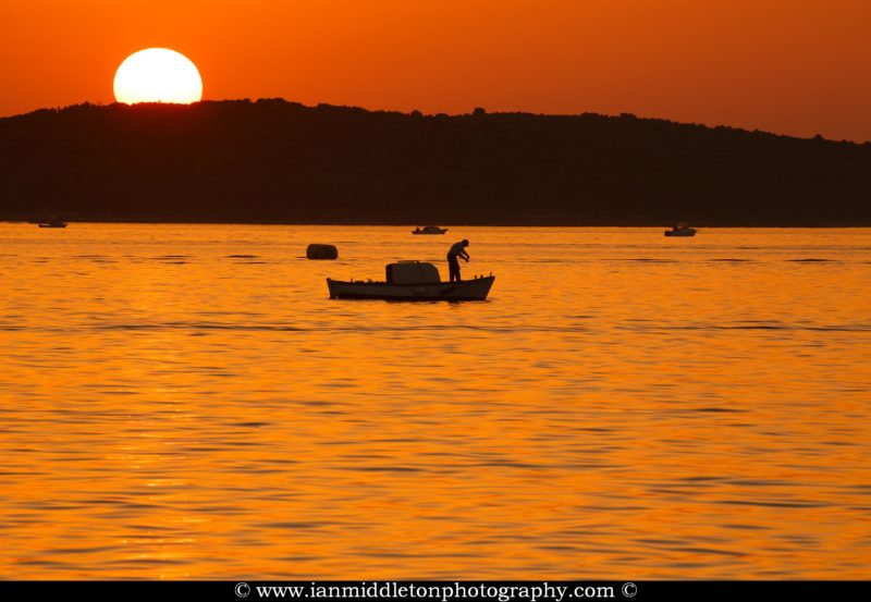 Fishing boats at sunset over the Brijuni Islands, Croatia. Seen from Puntižela Beach, Štinjan north of Pula.