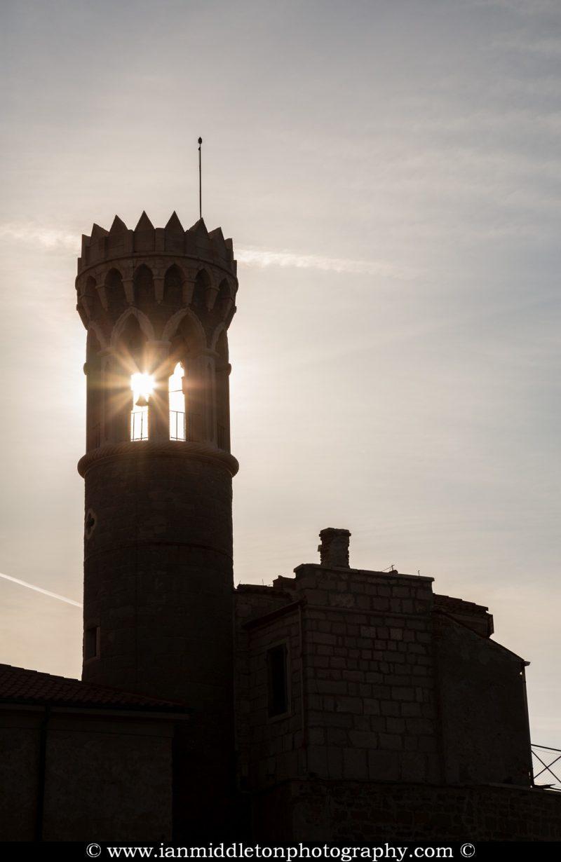 Sun bursting through the old Lighthouse in Piran, Slovenia