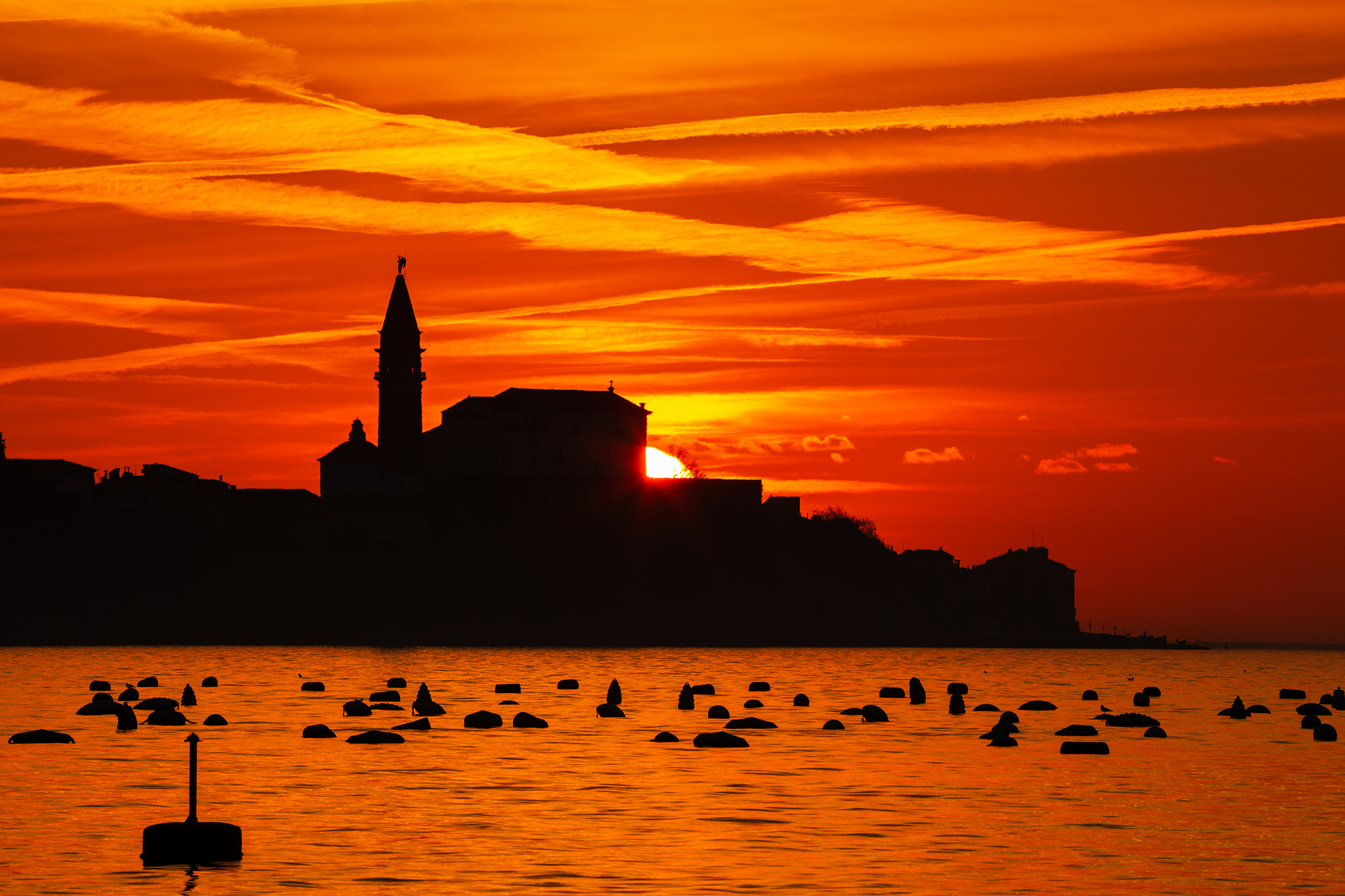 View of Saint George's Parish Church in Piran at sunset, seen from Strunjan, on the Adriatic Coast in Slovenia.