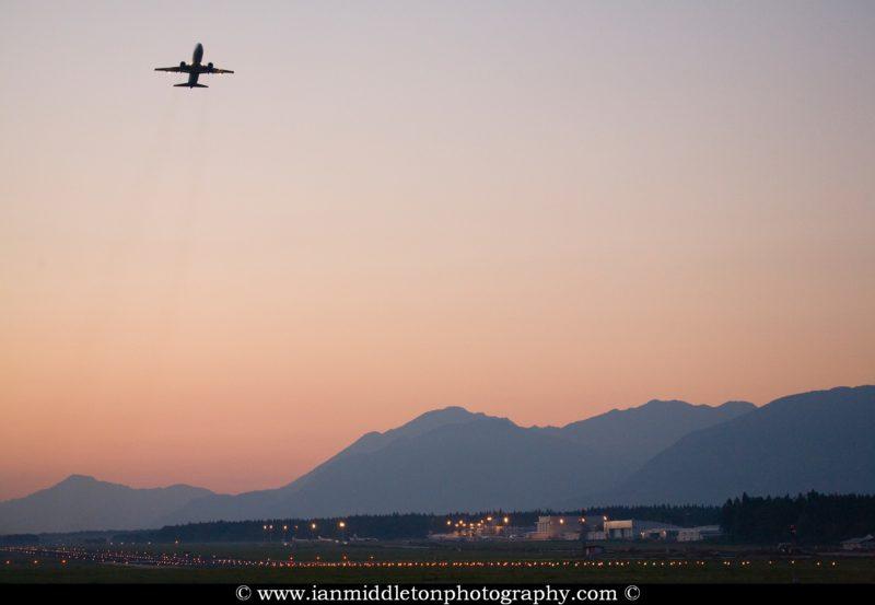 Aircraft taking off at dusk from Ljubljanas Joze Pucnik Airport in Brnik, Slovenia.