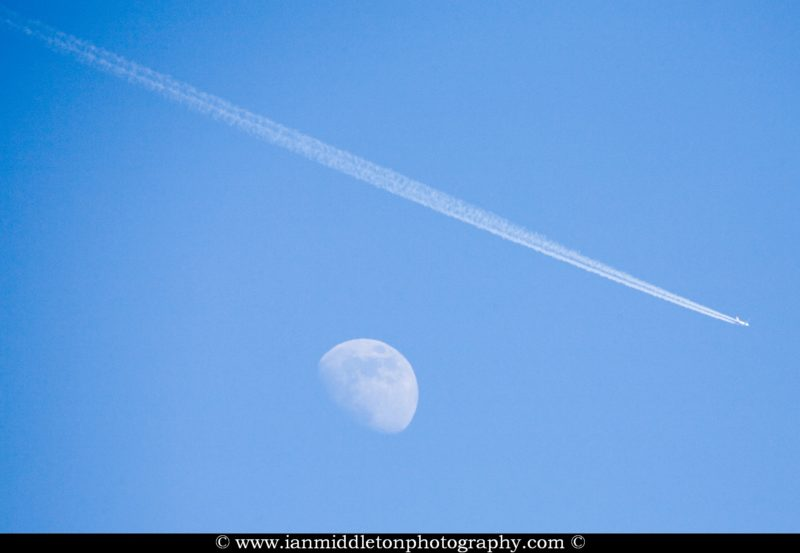 Aircraft flying over moon leaving vapour trail during the day, Shot from Ljubljana Airport, Slovenia.