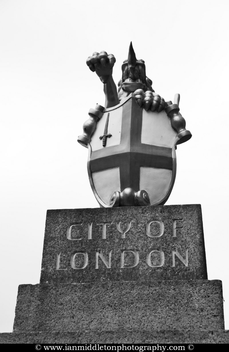 The City of London Dragon boundary mark at London Bridge. These cast iron statues of dragons mark the outer boundries of the city. This one is perched on a stone plinth, but some are also on metal plinths. The dragon is holding the a shield which bears the city's coat of arms painted in red and white. This is a replica of the originals at the Coal Exchange on Lower Thames Street.