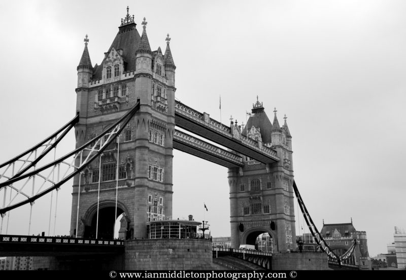 Black and white photo of Tower Bridge in London, England. This is a a combined bascule and suspension bridge, close to the tower of London and crosses the River Thames. It has become a distinctive landmark of the city.