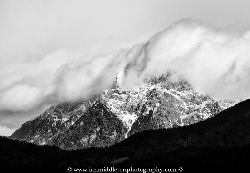 Black and white view Kalski Greben mountain (2224m) part of the Kamnik Alps as storm clouds gather around it.