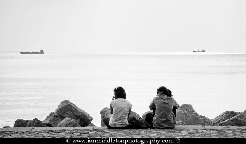 Two girls sitting on the promenade along viale miramare watching the ships go by in Trieste Bay, Italy.