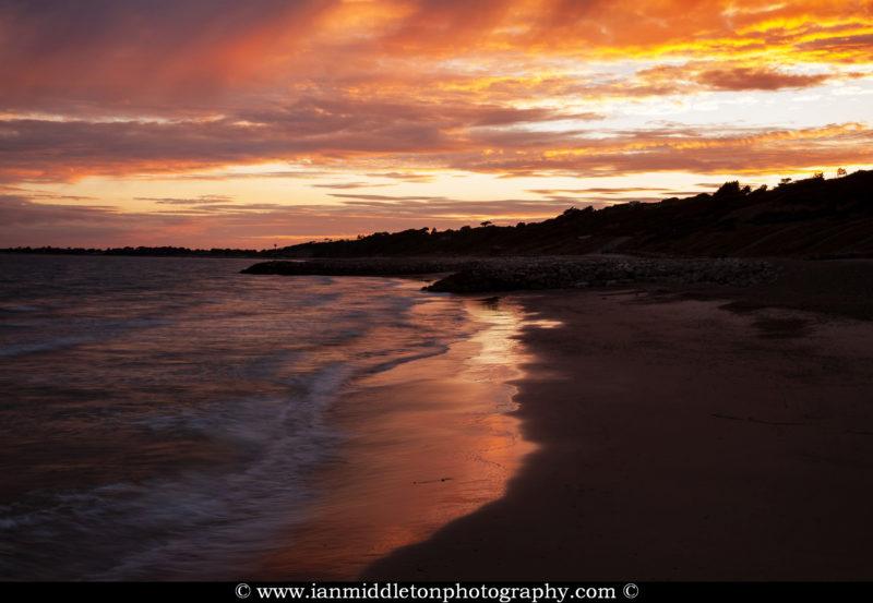 Sunset at Highcliffe Beach in Dorset.