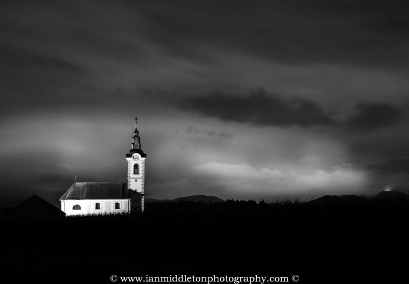 Black and white image of the the church of saint John (Sveti Janez) at dusk as storm clouds drift over, Brnik, Slovenia. In the distance on the lower right you can also see the baroque church of the mother of God glowing on Smarna Gora hill.