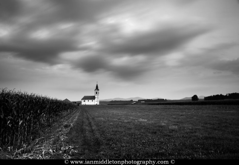 Black and white version of View of the the church of saint John (Sveti Janez) at dusk as storm clouds drift over, Brnik, Slovenia.