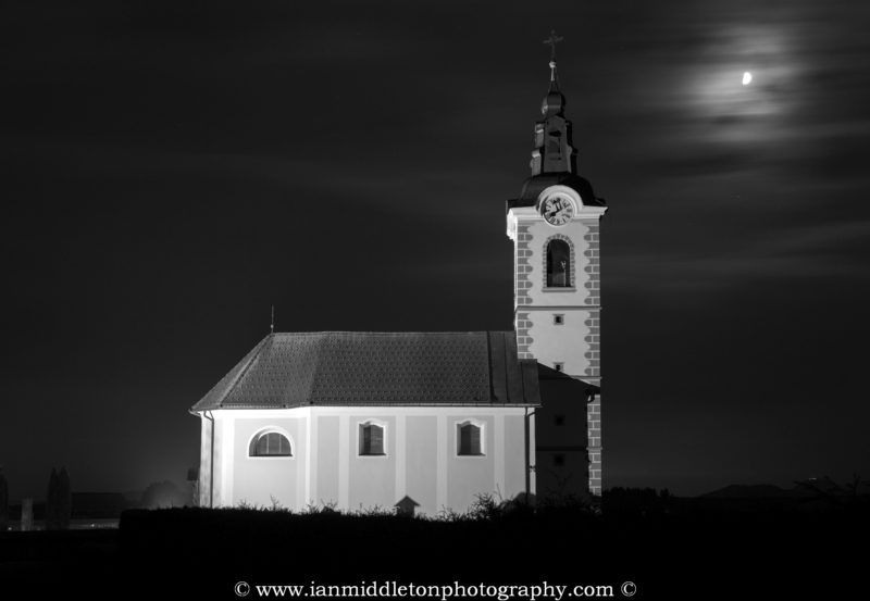 Black and white nightscape image of the church of saint John (Sveti Janez) just after dusk as clouds drift past the moon, Brnik, Slovenia. You can also see the church on Smarna Gora hill in the distance at the bottom right.