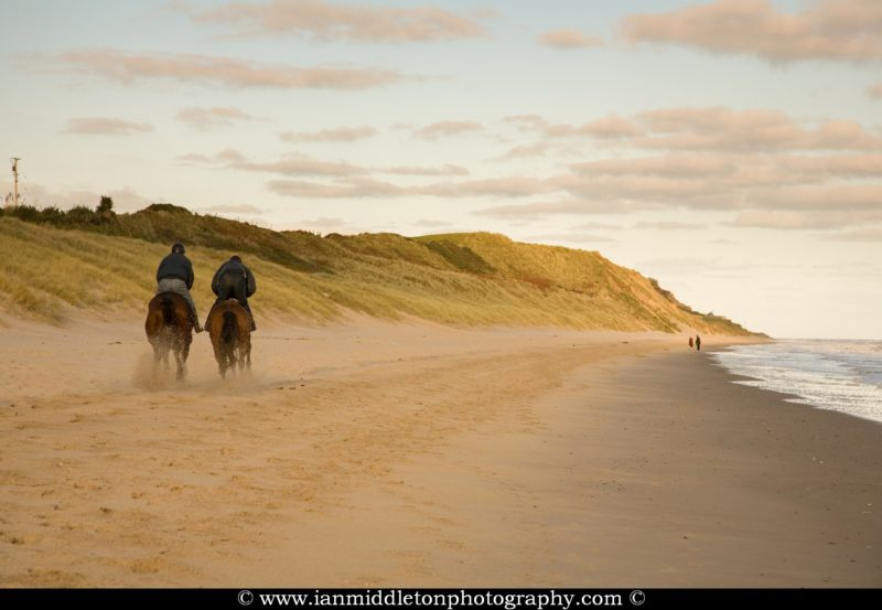 Horse riders on Blackwater beach, County Wexford, Ireland.