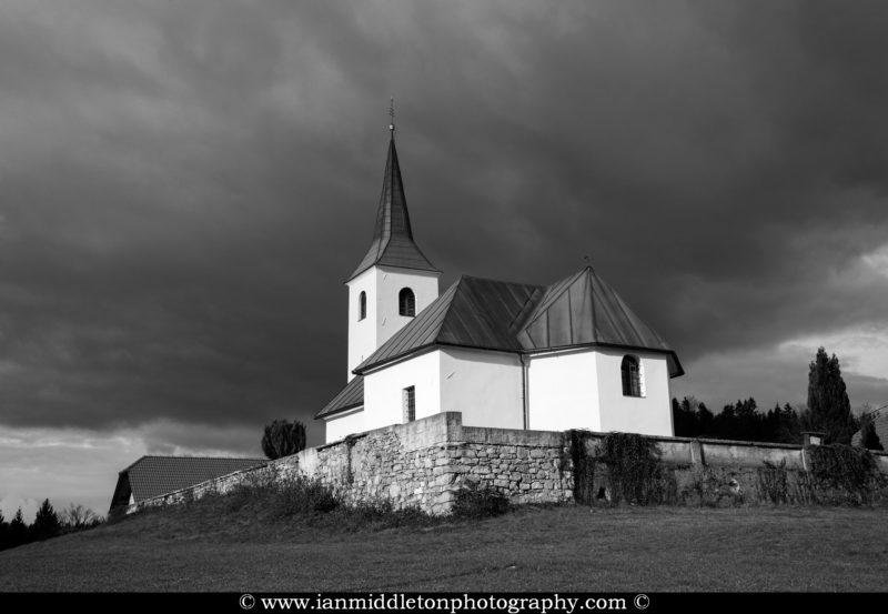 Sunlight breaks through the clouds and illuminates the church of Saint Mark (Sveti Marko) in Zapotok, Sodražica, Ribnica Municipality, Dolenjska, Slovenia