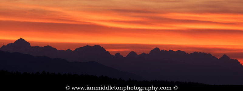 Panoramic view of the sun setting behind the Julian Alps mountains of Slovenia. This image is a 2 frame panoramic taken from a field in Brnik near Ljubljana Airport.