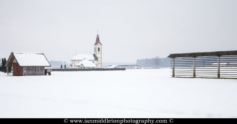 Winter view of the church of saint Simon and Jude as the snow falls, Brnik, near the Ljubljana airport, Slovenia. To the left is a farmer's hut and to the right is a Kozolec, a wooden rack for drying hay in the summer.