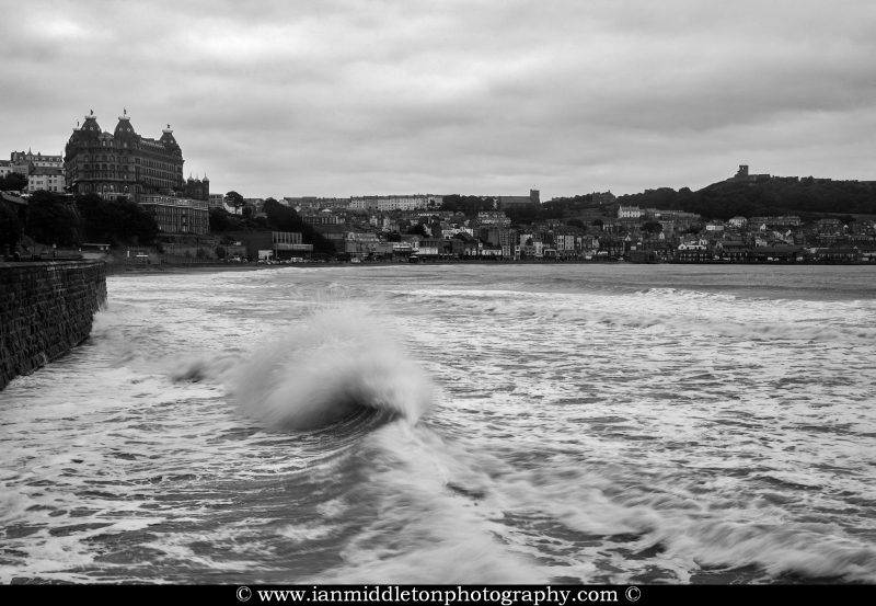 Waves crashing at high tide at Scarborough South Bay Beach and seawall, Yorkshire, England. You can see the Grand Hotel on the left and Scarborough Castle on the right.