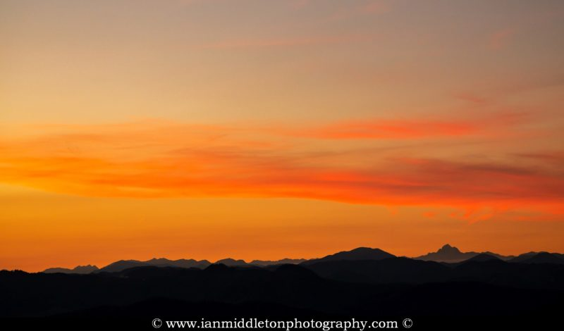 Sunset over the Julian Alps mountain range with Mount Triglav, the highest peak in Slovenia, clearly visible. Seen from a hill on the Ljubljana Marshes, Slovenia.