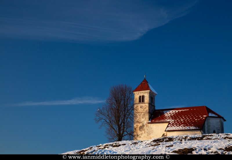 Church of Saint Anna in winter. Sveta Ana is perched upon an exposed hill overlooking the Ljubljansko Barje (Ljubljana marsh) near the village of Preserje. The views from this hill are spectacular and many locals seem to come here for the evening.