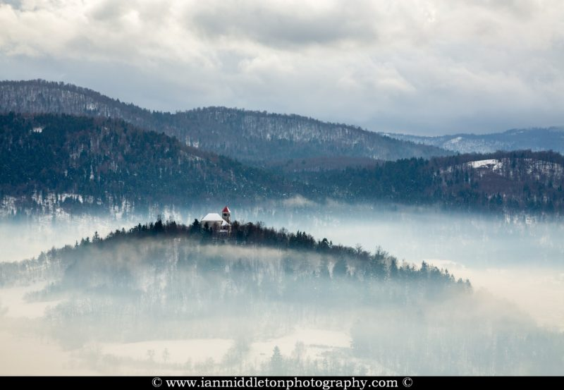 Mist surrounding the church of Sveti Josef (Saint Joseph), Slovenia. Seen from the church of Saint Anna (Sveta Ana). Sveta Ana is perched upon an exposed hill overlooking the Ljubljansko Barje (Ljubljana marsh) near the village of Preserje.