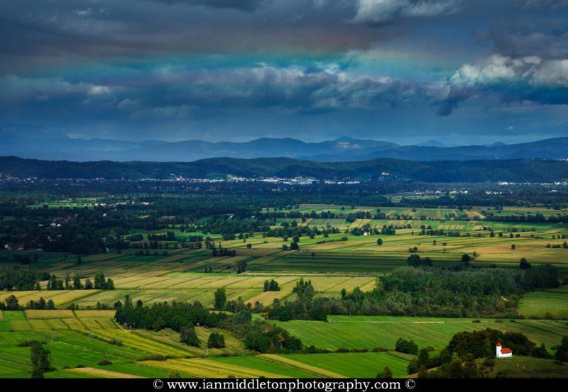 Faint rainbow over Ljubljana, seen from the hill of Sveta Ana across the Ljubljana Moors (Ljubljansko Barje) withThe church of sv. Lovrenc (Saint Lawrence) near Jezero in the foreground.