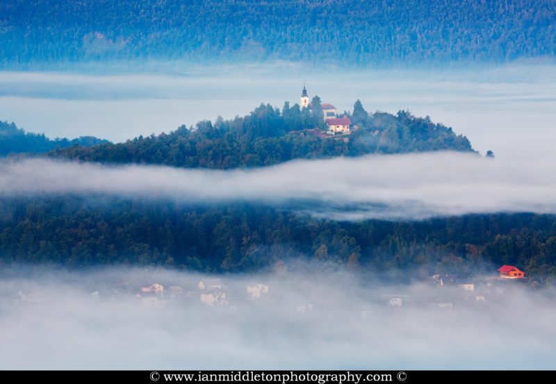 Mist in the valley enshrouding the church of Marija (Sveta Marija) and its hill on the Ljubjana Moors, Slovenia. Seen from the church of Saint Anna (Sveta Ana). Sveta Ana is perched upon an exposed hill overlooking the Ljubljansko Barje (Ljubljana marsh) near the village of Preserje.