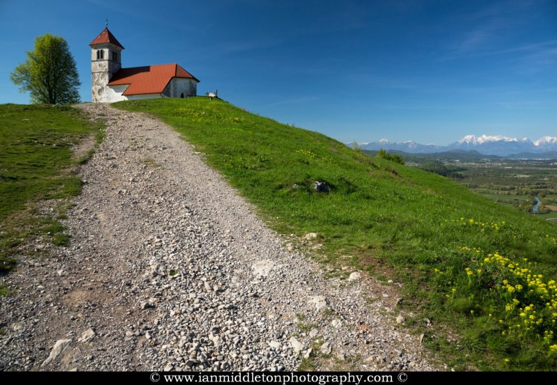 The path leadning up to church of Saint Anna (Sveta Ana) with Ljubljanica River and Kamnik Alps in the background. Taken in spring. Sveta Ana is perched upon an exposed hill overlooking the Ljubljansko Barje (Ljubljana marshes) near the village of Preserje. The views from this hill are spectacular and many locals seem to come here for the evening.