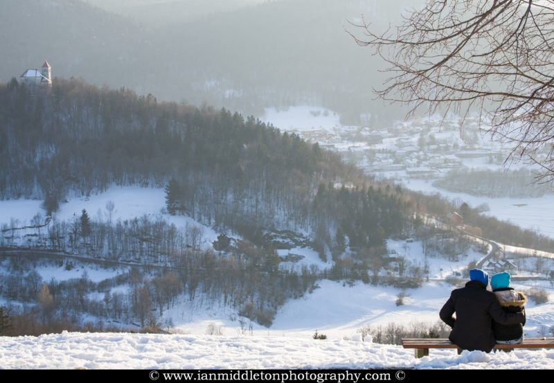 Couple sitting on a bench enjoying the evening view across to the church of Sveti Josef (Saint Joseph) from the church of Saint Anna (Sveta Ana). Sveta Ana is perched upon an exposed hill overlooking the Ljubljansko Barje (Ljubljana marsh) near the village of Preserje.