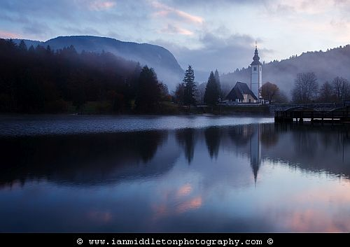 Morning mist and cloud over Lake Bohinj and the Church of Saint John at sunrise, Triglav National Park, Slovenia