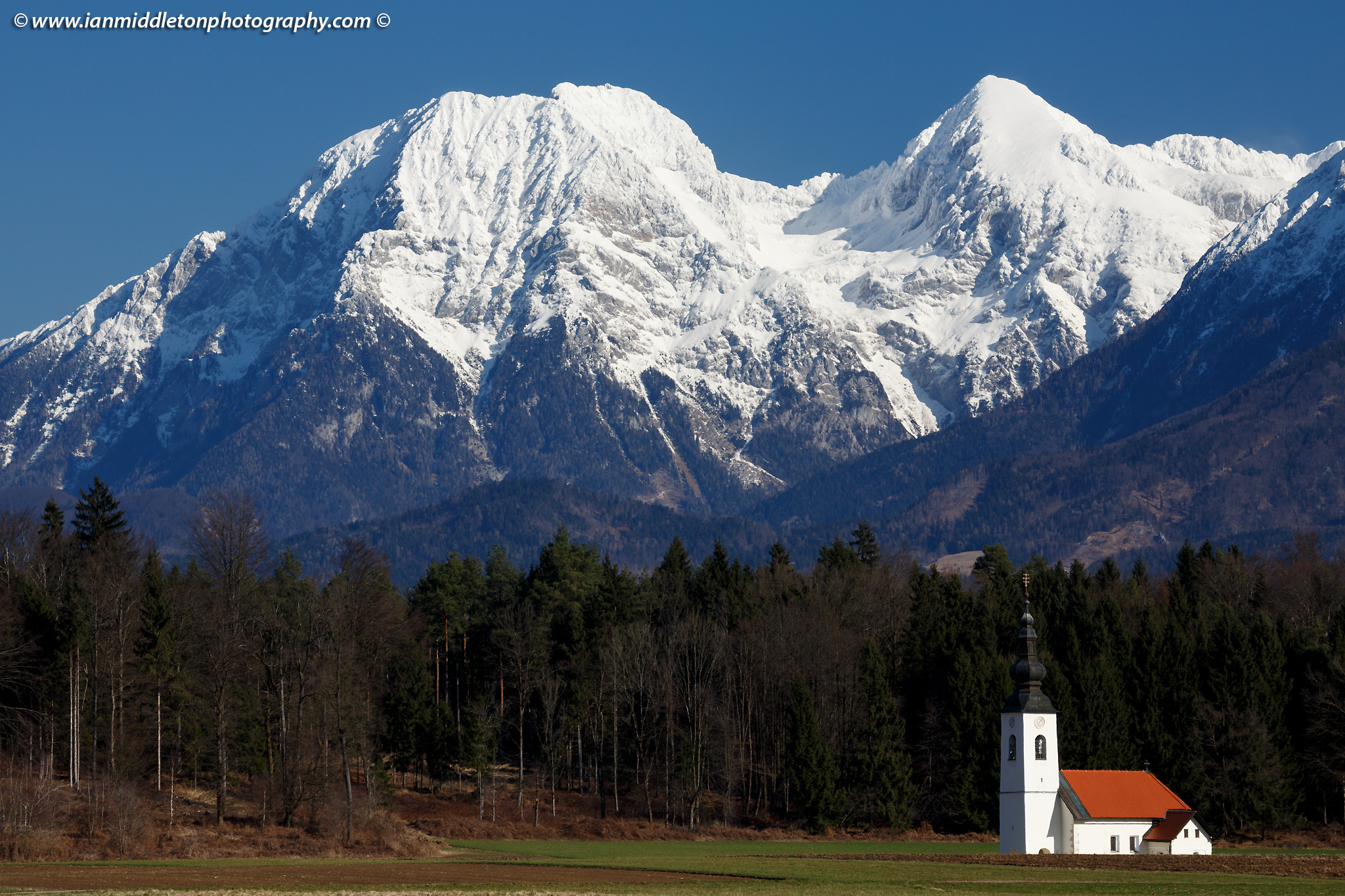 The church of Saint James in the little village of Hrase, near Medvode in Gorenjska, Slovenia, with the snowcapped Kamnik Alps behind.