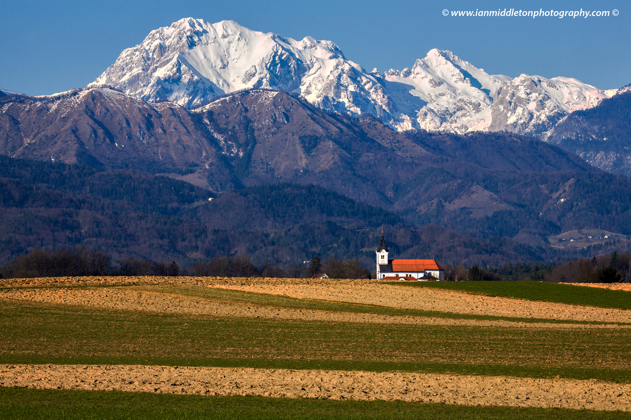 Mountaintops of the Kamnik Alps with the church of Saint Peter sitting in its shadow. This complex also contains a castle, a baroque church, a parsonage, a cemetery and a fairly large stable. The Alps have a fresh coating of snow after an abundance of snow this winter