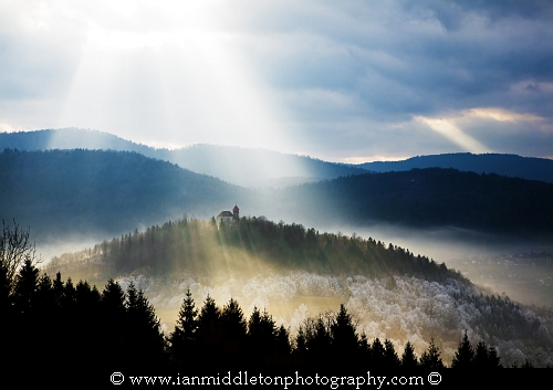 Afternoon sunrays falling over the church of Sveti Josef (Saint Joseph) seen from the church of Saint Anna (Sveta Ana). Sveta Ana is perched upon an exposed hill overlooking the Ljubljansko Barje (Ljubljana marsh) near the village of Preserje.