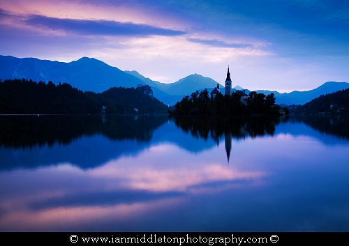 Sunset at Lake Bled and the island church of the assumption of Mary with the Karavanke mountains in the background, Slovenia. To the left of the church is Mount Stol, the highest peak in the Karavanke mountain range.