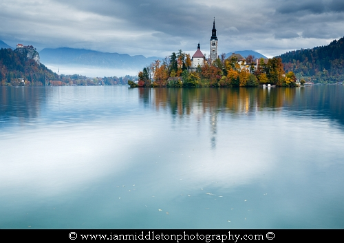 View across Lake Bled to the island church and clifftop castle in all it's autumn glory, Slovenia.