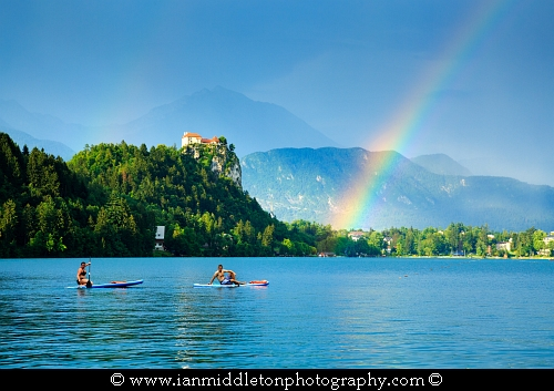 Beautiful light across to the beautiful Lake Bled's hilltop castle as a storm blows over and produces a rainbow. Slovenia.