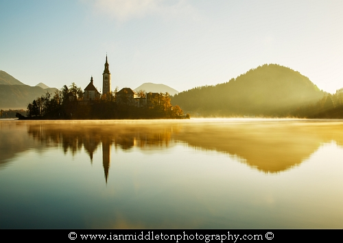 Warm morning sunlight over Lake Bled and the island church of the assumption of Mary, Slovenia.