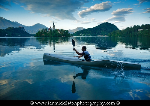 Man canoeing on Lake Bled, Slovenia with the island church of the assumption of saint mary, the clifftop castle in the background.