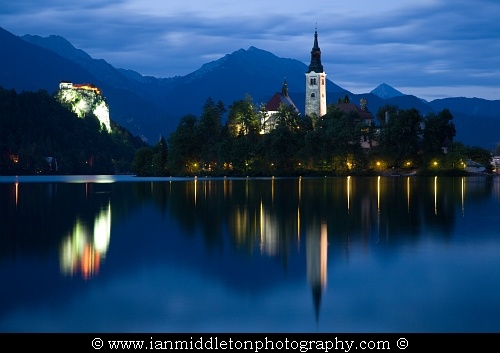 View across the beautiful Lake Bled, island church and hilltop castle at dusk with the beautiful Karawanke mountains in the background, Slovenia. Lake Bled is Slovenia's most popular tourist destination and the Karawanke mountains form the border between Slovenia and Austria.