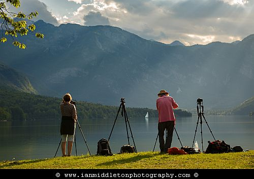 Participants on my photography workshop photographing beautiful light and clouds scattering over Bohinj Lake, ,Triglav National Park, Slovenia.