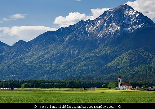 View of the the church of saint John in the shadow of Storzic mountain, Brnik, near the Ljubljana airport, Slovenia. At 2132m Storzic is one of the highest peaks in the Kamnik Alps mountain range.