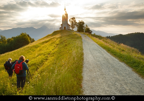 Photography workshop students at work at Jamnik church of Saints Primus and Felician, perched on a hill on the Jelovica Plateau with the kamnik alps and storzic mountain in the background, Slovenia.
