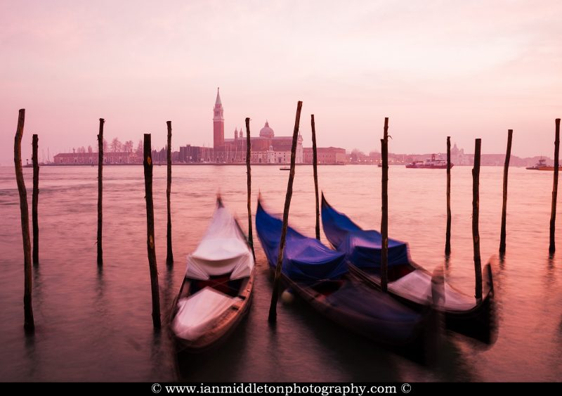 Gondolas at sunset over the Grand Canal in Venice, Italy.