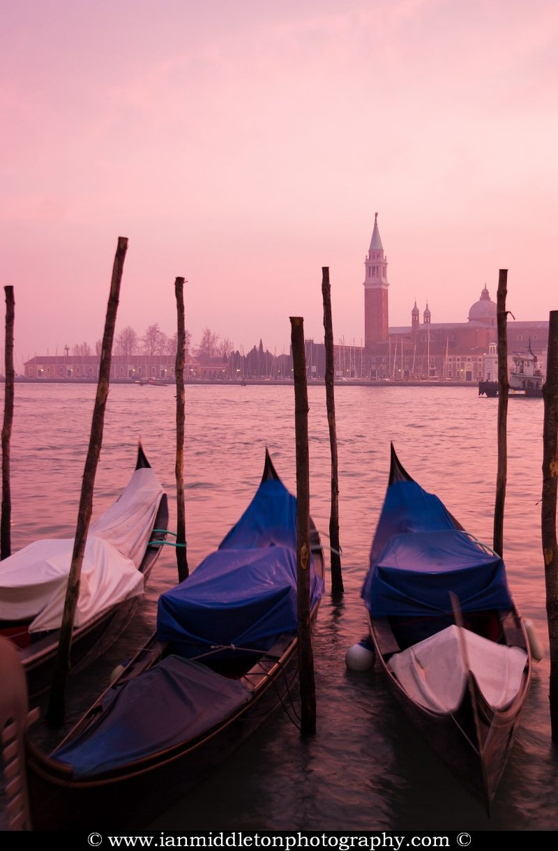 Photo of Venice and gondolas at sunset over the Grand Canal, Italy.