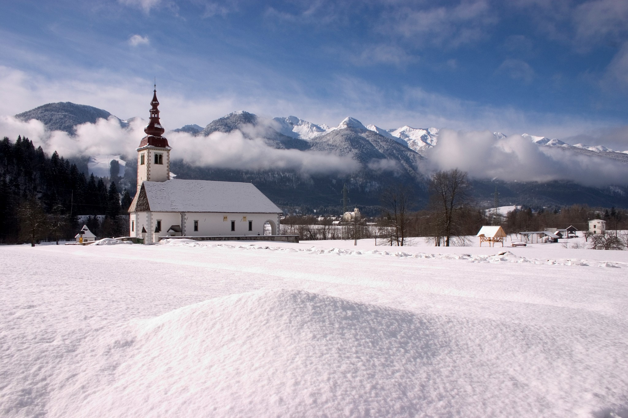 Winter view of the church of the assumption of Mary in Bitnje, a village just outside Bohinjska Bistrica, Bohinj valley, Triglav National Park, Slovenia. You can also see the Church of Saint Nicholos in Bohinjska Bistrica in the background.